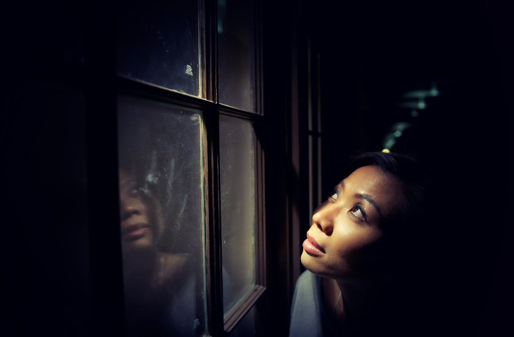 A dark-skinned woman looking out a window toward a night sky. Image by Pexels from Pixabay: https://pixabay.com/photos/alone-dark-female-girl-light-1867056/